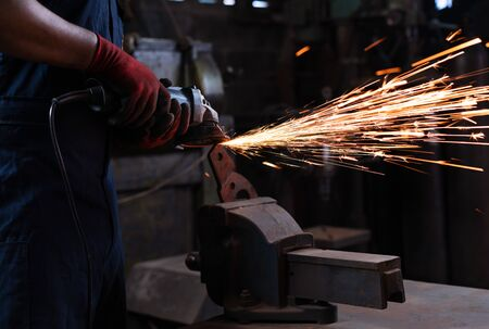 Metal worker using power tools in manufacturing facility, cutting and shaping metal during work shift - View of engineering industry student using heavy duty equipment in workshop