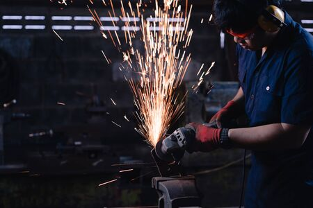 Asian industrial metal worker wearing protective clothing and using power tools and equipment in dark production facility with bright hot sparks and copy space