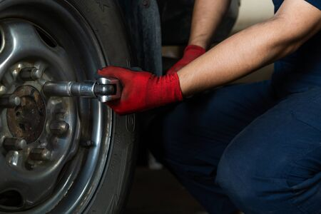 Automotive engineer operating hand tools on car in repair centre, while replacing wheel and tires - Maintenance technician servicing truck during routine vehicle service inspection