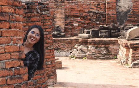 Fun loving young diverse Asian girl hiding behind brick wall and smiling - Millennial hipster social influencer travelling to cultural tourist destinations - Travel, trends and vacation ideas concept