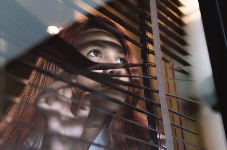 Asian woman looking through window blinds spying on neighbours - Young lonely millennial woman peeping through glass observing gossip and action outdoors - introvert, spy and intrusive concepts 版權商用圖片
