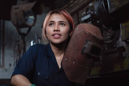 Diverse female industrial engineer holding welding helmet after work shift - Young Asian factory metal worker taking a break - Hispanic apprentice woman, learning new skills on internship training 版權商用圖片