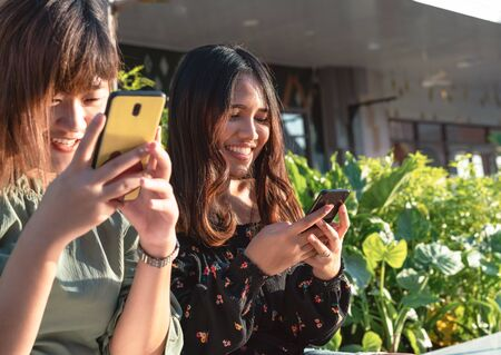 Young millennial Asian friends hanging out outdoors instant messaging on smartphones - Happy smiling hipster girls chatting on social media using mobile phone - Leisure, lifestyle and pals concept