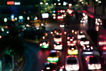 Defocussed urban traffic background at night with colourful bokeh - Blurred city congestion road junction backdrop, with glare from nearby shops and cars with copy space -Metropolis downtown concept 版權商用圖片