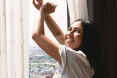 Young diverse woman yawning and stretching out of apartment block window - Sleepy head tired millennial Asian girl waking up late to bright morning sunshine - Weekend, lazy and fresh concept