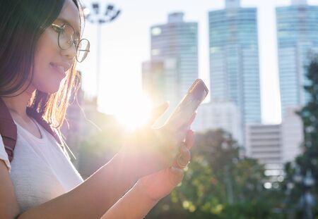 Diverse Asian girl looking at smart phone in urban city park with bright afternoon sunshine - Young millennial hipster student woman holding mobile device outdoors - One person solo travel concept