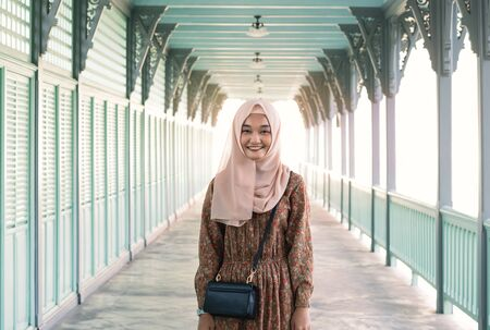 Young and happy Asian muslim girl standing outdoors with bright afternoon sunshine behind her - Smiling millennial woman wearing religious headscarf and floral dress - Culture and diversity concept