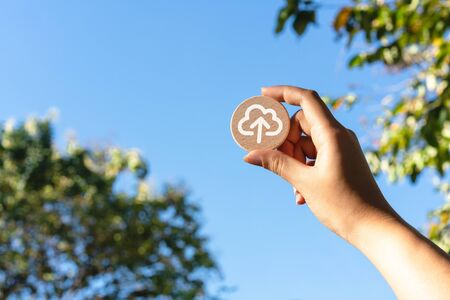 Diverse Asian female hand holding up wood disc with cloud computing upload icon - Cloud computer file transfer symbol with blue sky - Remote connectivity, data storage and digital security concepts