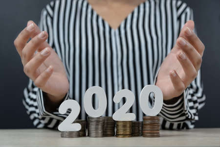 2020 on top of stacks of coins with open palms of a female above - business finance concept