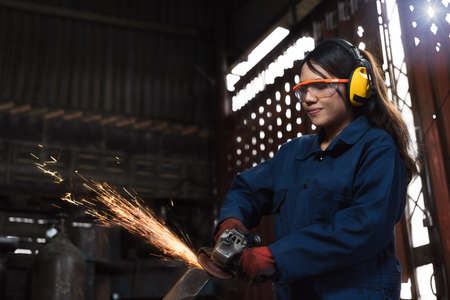 Young diverse female mechanic using factory equipment to cut metal wearing safety workwear and equipment