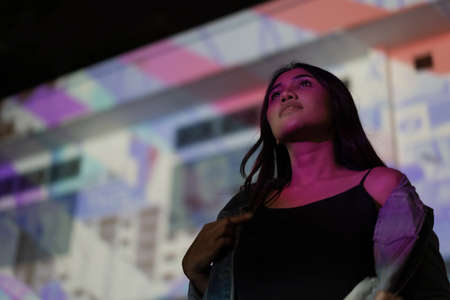 Young hipster woman standing outdoors at night in front of light projector with pink light projected on her body and face