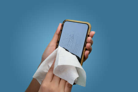Hands cleaning cell phone with antibacterial disinfectant wipes