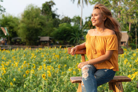 Young diverse woman sitting and smiling in afternoon with sunflower 版權商用圖片