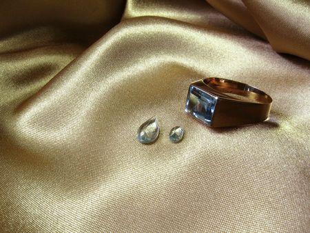 An aquamarine gold ring with two gems on gold satin.