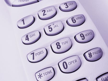 Close-up view of a cordless phone, showing numerical keypad, purple hue