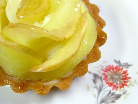A tartelette aux pommes, or apple tart, on a floral white plate Stock Photo
