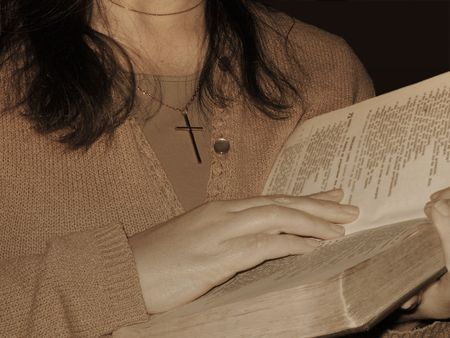Woman with cross pendant holding and reading the Bible.