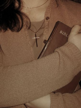 Woman with cross pendant holding the Bible to the chest.