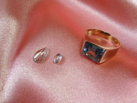 pink satin: An aquamarine gold ring with two gems on pink satin.