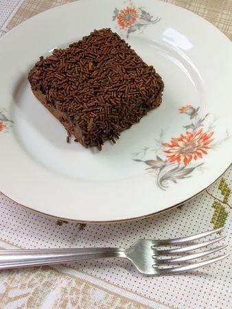 A delicious chocolate brownie covered with chocolate flakes on a floral white plate.