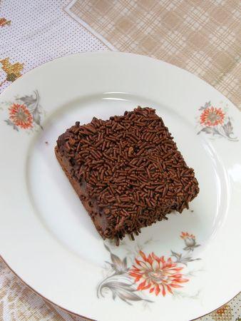 Un brownie squisito del cioccolato coperto di cioccolato si sfalda su una piastra bianca floreale.