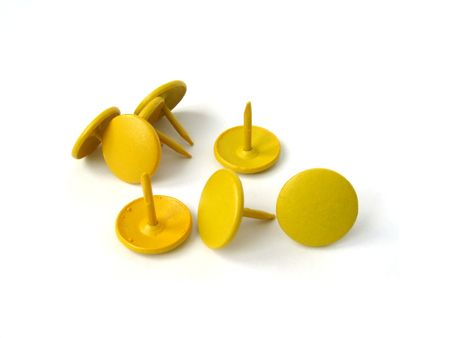 A bunch of yellow thumbtacks, or drawingpins, isolated on white. Stock Photo