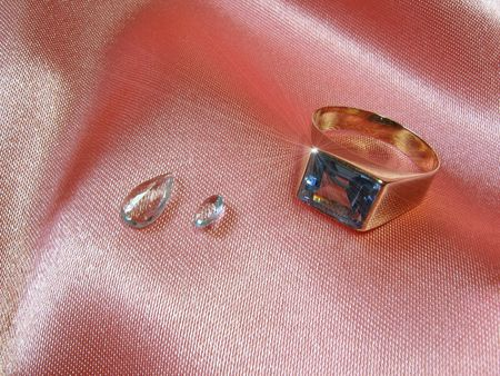 An aquamarine gold ring with two gems on pink satin. The sparkle was digitally added. Most of the raw aquamarine crystals for the world market come from the gemstone mines of Brazil. Its name is derived from the Latin aqua (water) and mare (sea).