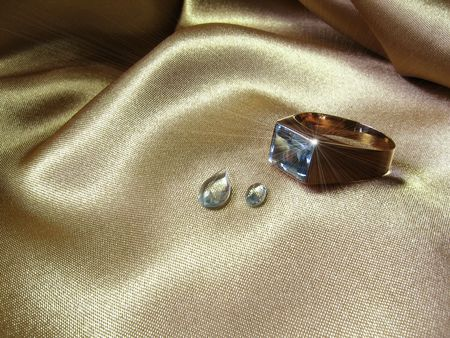 An aquamarine gold ring with two gems on gold satin. The sparkle was digitally added. Most of the raw aquamarine crystals for the world market come from the gemstone mines of Brazil. Its name is derived from the Latin aqua (water) and mare (sea). Stock Photo