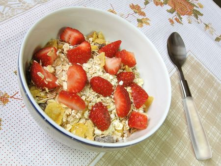A bowl of granola and strawberries on a floral towel.