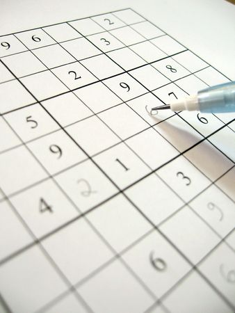 A partially filled sudoku puzzle with pencil.  Sudoku is an addictive Japanese math puzzle whose aim is to fill in a grid so that every row, every column, and every 3x3 box contains the numbers 1 to 9. Stock Photo