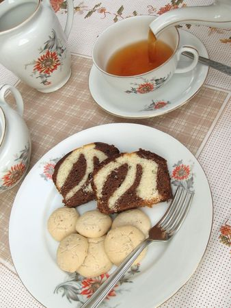 A table set for tea, with tea being poured and a plate of cake and cookies Stock Photo