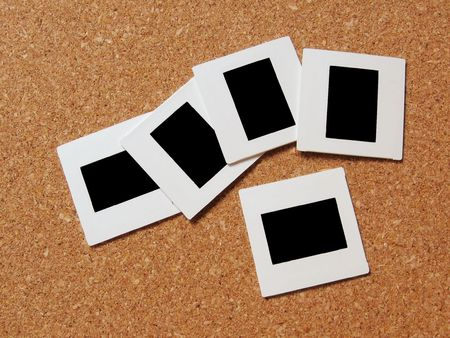 Photo slides and frames on a board. Images can be inserted in the blank frames.