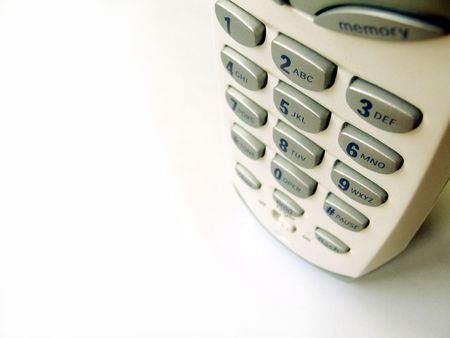 Close up top view of a cordless phone on white background, shallow DOF, with copy space