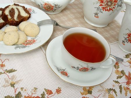A table set for tea, with a tea cup, pots and a plate of cake and cookies