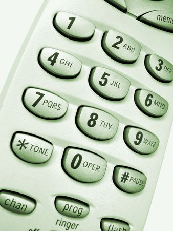 Close up view of a cordless phone, showing numerical keypad, green hue.