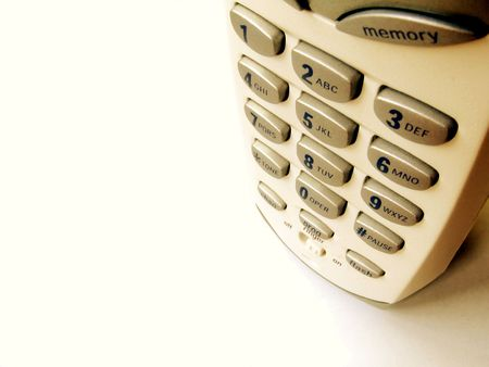 Close up top view of a cordless phone on white background, deep DOF, golden hue, with copy space. Stock Photo