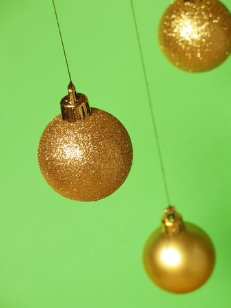 Glittering golden Christmas balls hanging above a green background