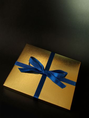 Close up view of a gold gift box with blue bow on black background, with copy space and exquisite lighting