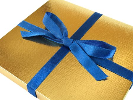 Close up view of a gold gift box with blue bow on white background Stock Photo