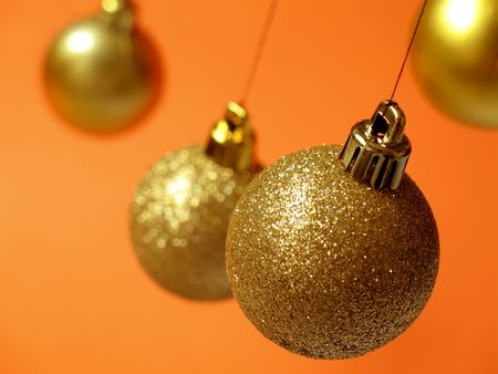 Glittering golden Christmas balls hanging above an orange background photo