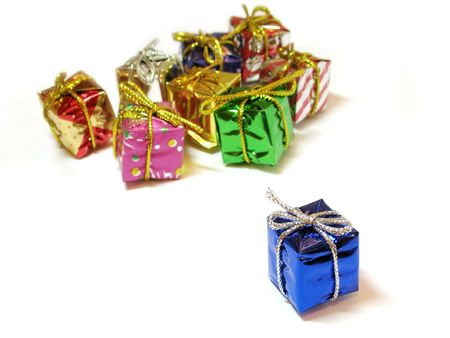 Colorful decorative mini gift boxes on white background, one focused in the foreground, the others unfocused in the background