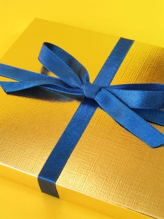 ornated: Chiudasi sulla vista di un contenitore di regalo delloro con larco blu su priorit� bassa gialla luminosa