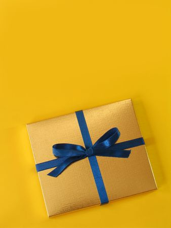 Close up view of a gold gift box with blue bow on bright yellow background, with copy space Stock Photo - 644147
