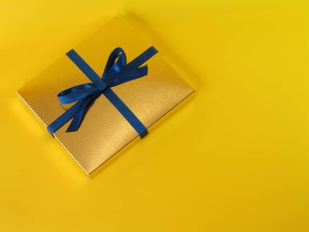 Close up view of a gold gift box with blue bow on bright yellow background, with copy space Stock Photo