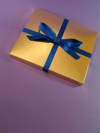Close up view of a gold gift box with blue bow on violet background, with copy space and exquisite lighting Stock Photo - 644149