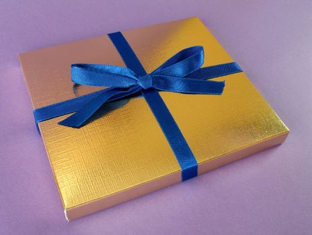 Close up view of a gold gift box with blue bow on violet background