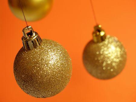 Glittering golden Christmas balls hanging above an orange background