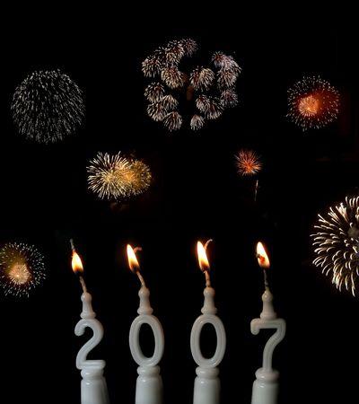 Capodanno celebrazione: la masterizzazione di candele mostrando l'anno 2007, con fuochi d'artificio in background
