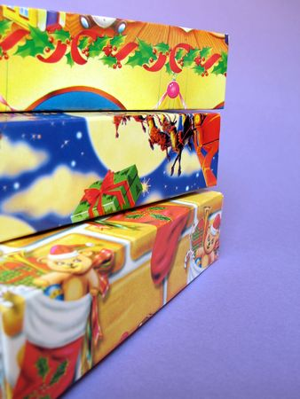 Close up view of a stack of three colorful Christmas gift boxes on violet background, with shallow DOF