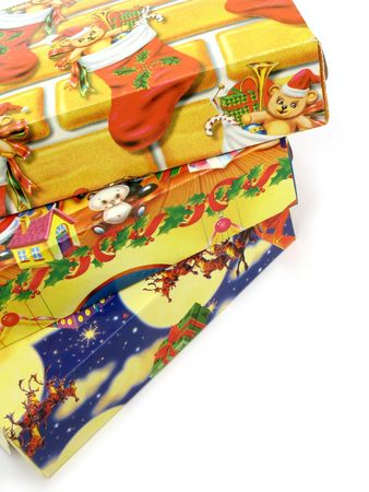 Close up view of a stack of three colorful Christmas gift boxes on white background, with copy space